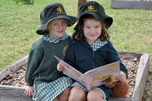 Holly Armstrong and Jemima Donnelly sharing a book in the playground during  Catholic Schools Week.