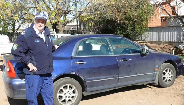 Sergeant Peter Gibson pictured with a stolen car involved in a police pursuit in Condobolin last week. DG